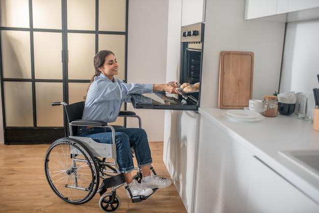 Tareas del hogar. una niña en silla de ruedas haciendo tareas domésticas y mirando involucrada
