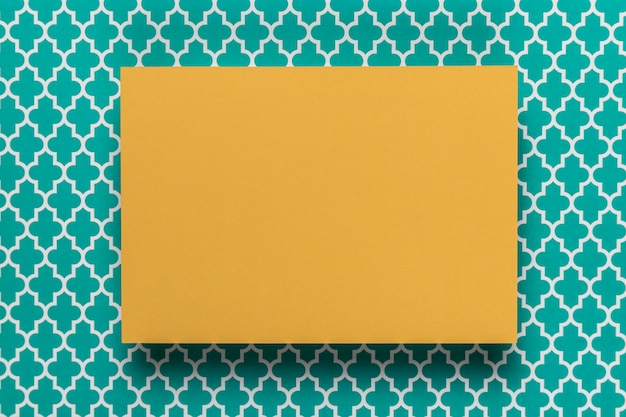 Tarjeta amarilla sobre fondo verde azulado