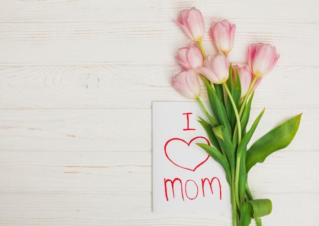 Tarjeta amo a mamá y flores colocadas en mesa de madera blanca