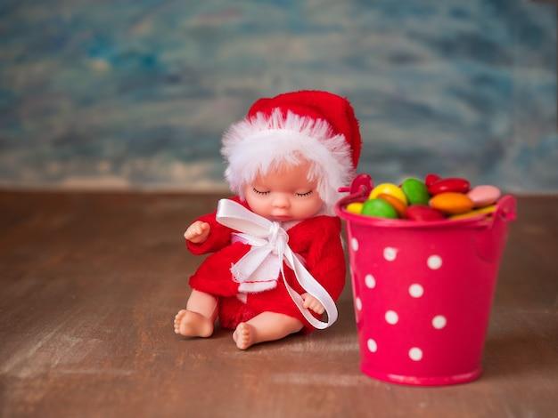 Tarjeta de año nuevo para niños el pequeño santa se sienta junto a un cubo de caramelo de colores