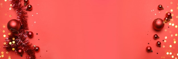 Tarjeta de año nuevo o navidad con bolas rojas brillantes y oropel sobre un fondo rojo con copyspace
