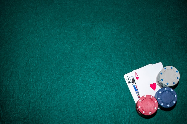 Tarjeta de as de jack of spade y corazón con pila de fichas de casino en mesa de póquer verde