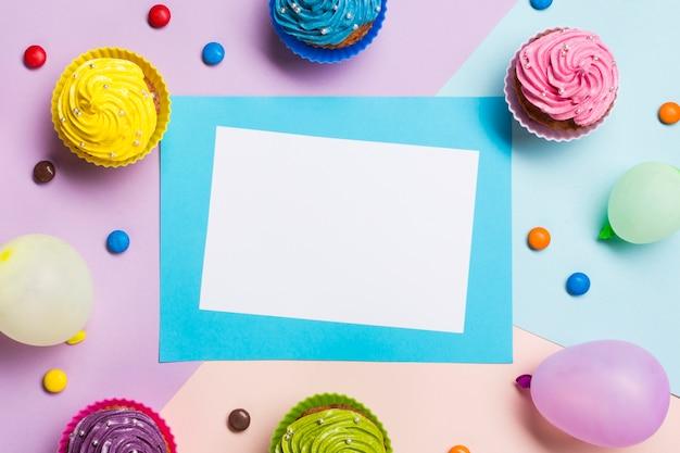 Tarjeta azul y blanca en blanco rodeada de globo; muffins y gemas sobre fondo coloreado