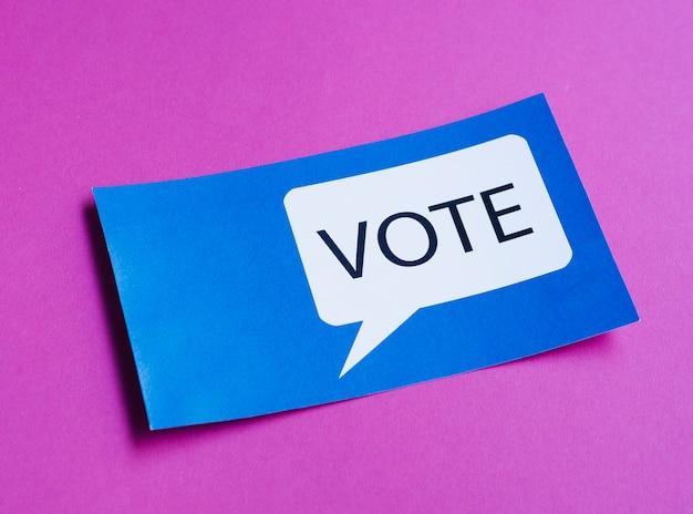 Tarjeta azul con bocadillo de votación sobre fondo morado