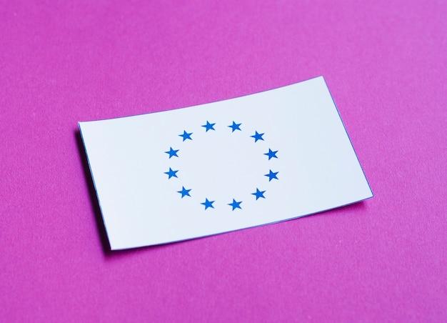 Tarjeta blanca con bandera europea sobre fondo morado