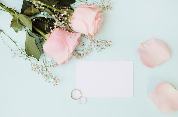 Tarjeta blanca en blanco con anillos de boda y rosas sobre fondo azul pastel