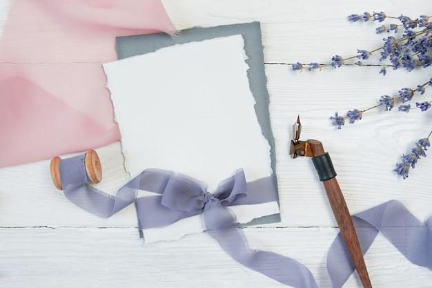 Tarjeta blanca en blanco arco de cinta sobre un fondo de tela rosa y azul con flores de lavanda y pluma caligráfica