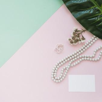 Tarjeta blanca en blanco con collar de perlas, flores y hojas en el telón de fondo
