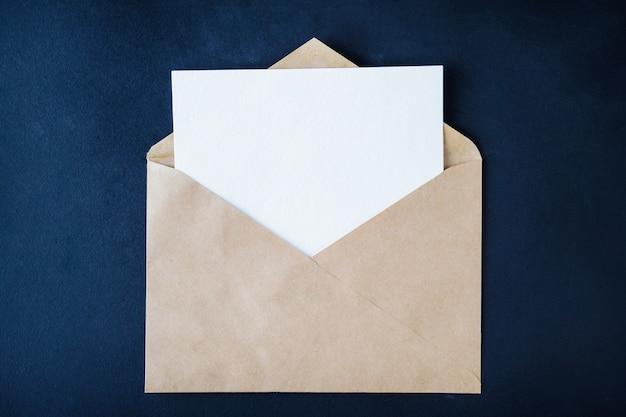Tarjeta blanca en blanco en marrón enveloop sobre fondo oscuro