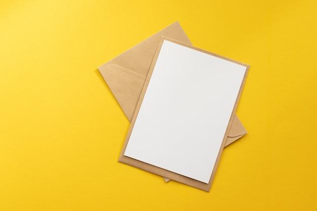 Tarjeta blanca en blanco con plantilla de sobre de papel marrón kraft maqueta sobre fondo amarillo