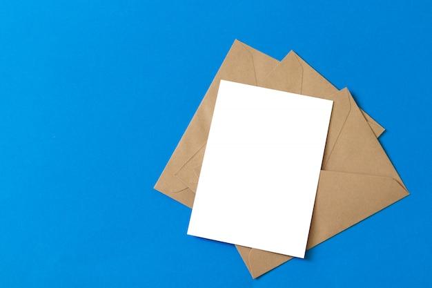 Tarjeta blanca en blanco con plantilla de sobre de papel marrón kraft maqueta