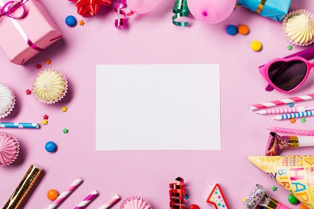 Tarjeta blanca en blanco rodeada con artículos de cumpleaños sobre fondo rosa
