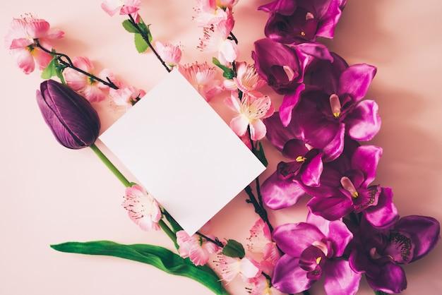 Tarjeta blanca para mock up con hermosas flores de fondo.