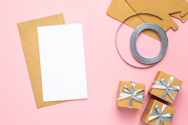 Tarjeta blanca con regalo en composición de caja para cumpleaños sobre fondo rosa