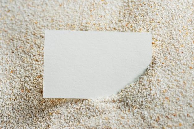 Tarjeta blanca sobre arena.