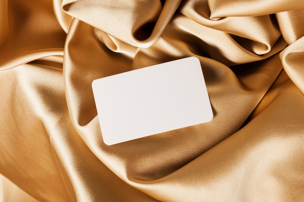 Tarjeta blanca sobre tela dorada