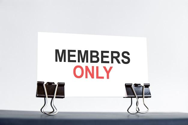 Una tarjeta blanca con texto exclusivo para miembros se encuentra en clips sobre un escritorio contra el fondo azul claro. desenfocado.