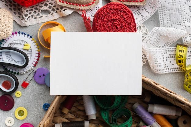 Tarjeta blanca vacía y accesorios coloridos de mercería