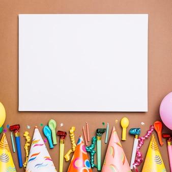 Tarjeta en blanco blanca con objetos de cumpleaños sobre fondo marrón