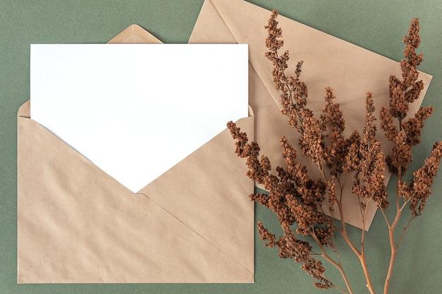 Tarjeta en blanco blanca, sobre artesanal y planta de flores secas sobre fondo verde. vista superior espacio plano de copia de maqueta.