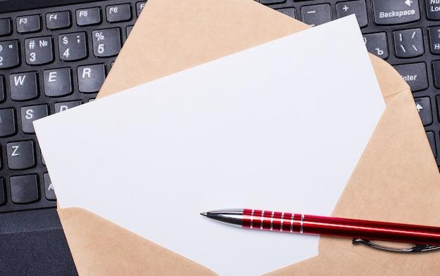 Tarjeta en blanco blanca con sobre de artesanía en la mesa de trabajo con teclado de portátil moderno y bolígrafo color burdeos. disposición plana del lugar de trabajo. copie el espacio.