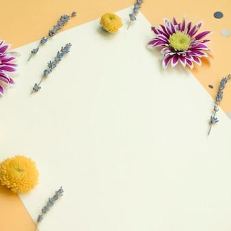 Tarjeta en blanco decorada con flores sobre el fondo amarillo