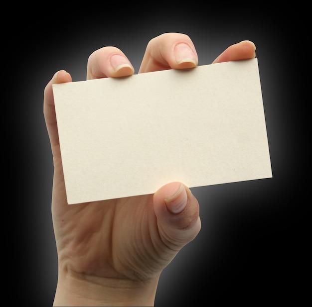 Tarjeta en blanco en una mano sobre el blanco