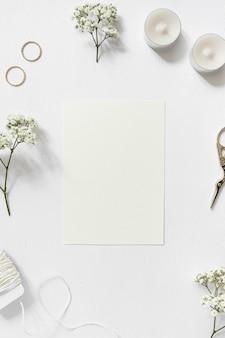 Tarjeta en blanco rodeada con gypsophila; anillos de boda; cadena y tijera sobre fondo blanco