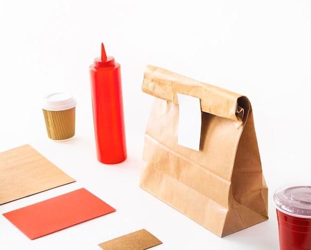 Tarjeta en blanco con taza de café; botella de salsa; y paquete sobre fondo blanco