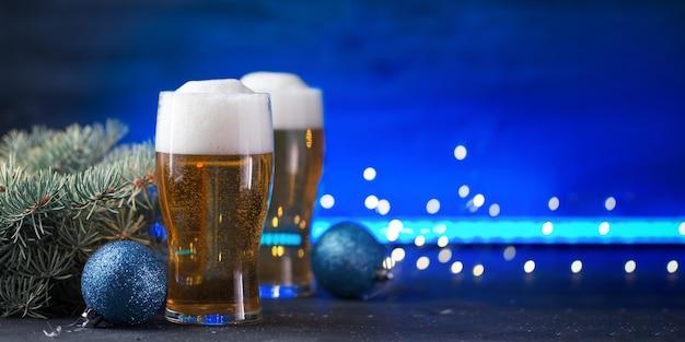 Tarjeta de brindis de navidad, dos vasos de cerveza ligera sobre un fondo de neón de color con guirnaldas y espacio de copia