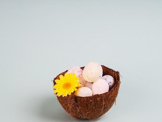 Tarjeta de celebración de pascua - enfoque selectivo de huevos de pascua de colores naturales huevos en cáscara de coco, flores de gypsophila, fundamento rosa, estilo rústico