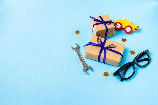 Tarjeta de concepto del día del padre con la herramienta de trabajo del hombre sobre fondo azul y cajas de regalos envueltas en papel kraft
