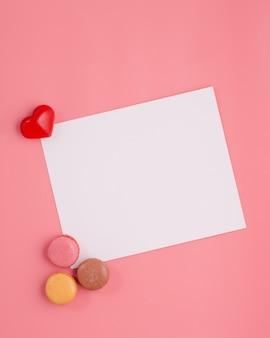 Tarjeta con corazón y macarrones sobre fondo rosa