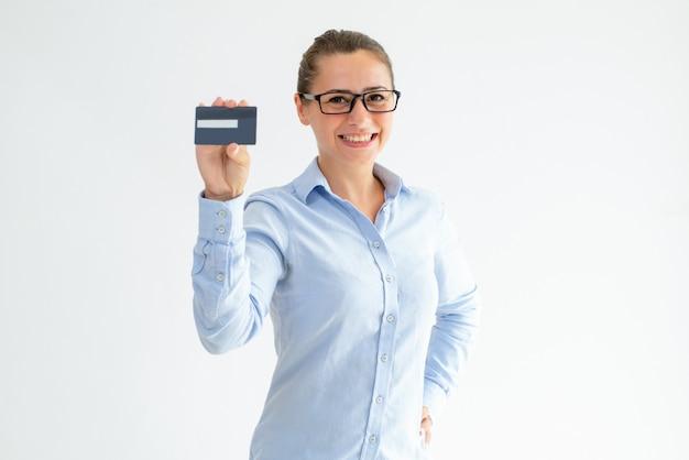 Tarjeta de crédito alegre de la publicidad de la muchacha de oficina