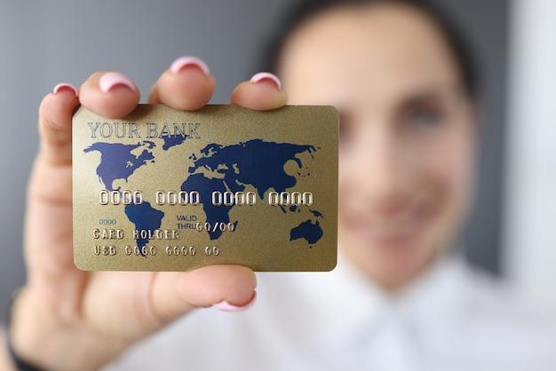 Tarjeta de crédito bancaria en el fondo de la mujer sonriente