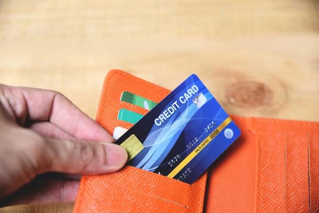 Tarjeta de crédito en billetera con mano.