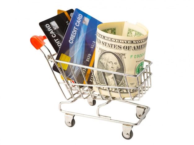 Tarjeta de crédito y billetes de dólar en carro de compras en blanco.