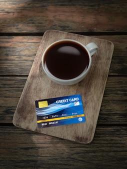 Tarjeta de crédito en blanco con una taza de café en la mesa de madera