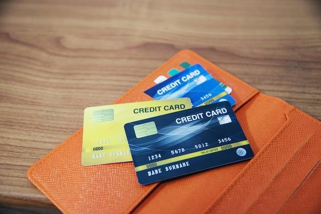Tarjeta de crédito en cartera sobre la mesa de madera.