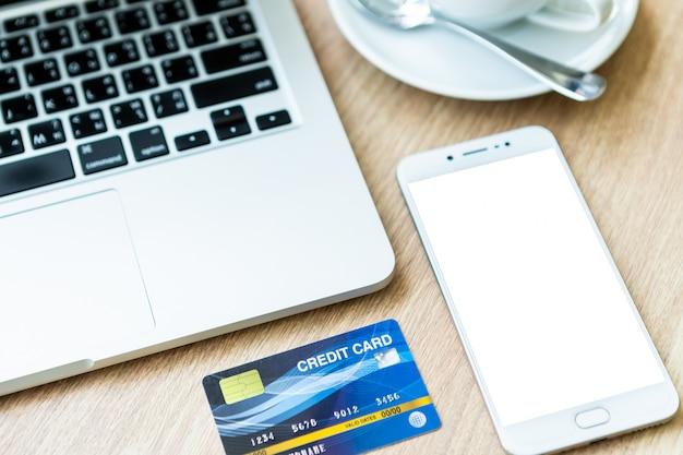 Tarjeta de crédito de computadora portátil, teléfono inteligente y taza de café en madera