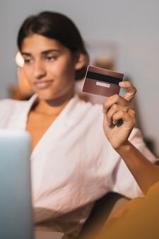 Tarjeta de crédito dorada sujeta por hermosa mujer