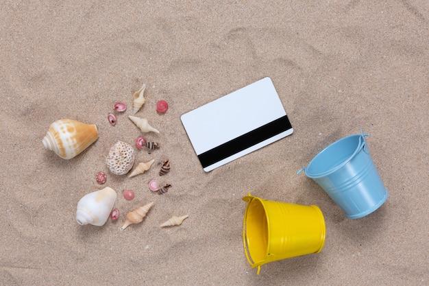 Tarjeta de crédito y elementos de verano en la arena