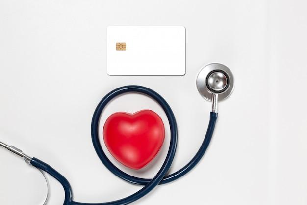 Tarjeta de crédito y estetoscopio con corazón rojo
