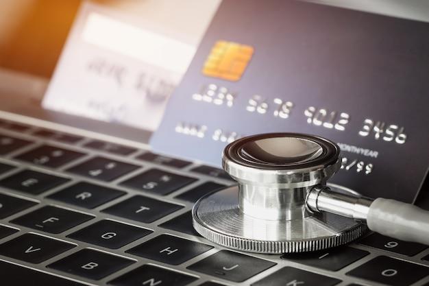 Tarjeta de crédito con estetoscopio en tarjeta de crédito con computadora en tarjeta en hospital