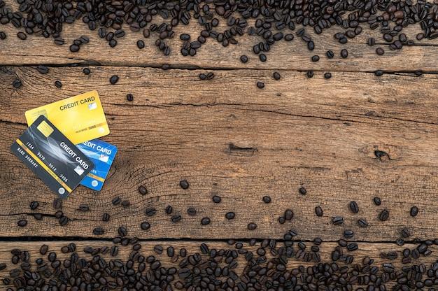 Tarjeta de crédito y granos de café en el escritorio, vista superior