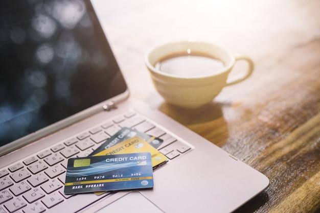 Tarjeta de crédito en laptop con taza de café