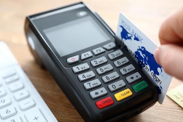Tarjeta de crédito de mano masculina con terminal pos primer plano