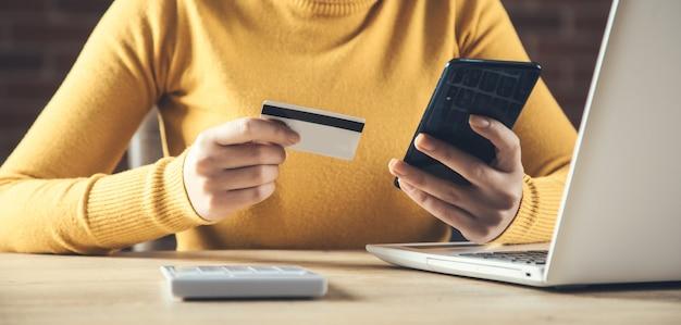 Tarjeta de crédito de mano de mujer y teléfono con computadora en la mesa