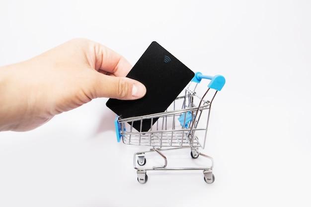 Tarjeta de crédito en mano y un pequeño carrito de la compra sobre un fondo blanco.