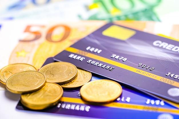 Tarjeta de crédito con monedas y billetes en euros.